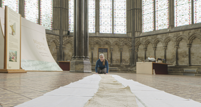 Salisbury Cathedral Archivist Emily Naish with a scroll