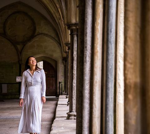 Woman walking through the cloisters in Salisbury Cathedral